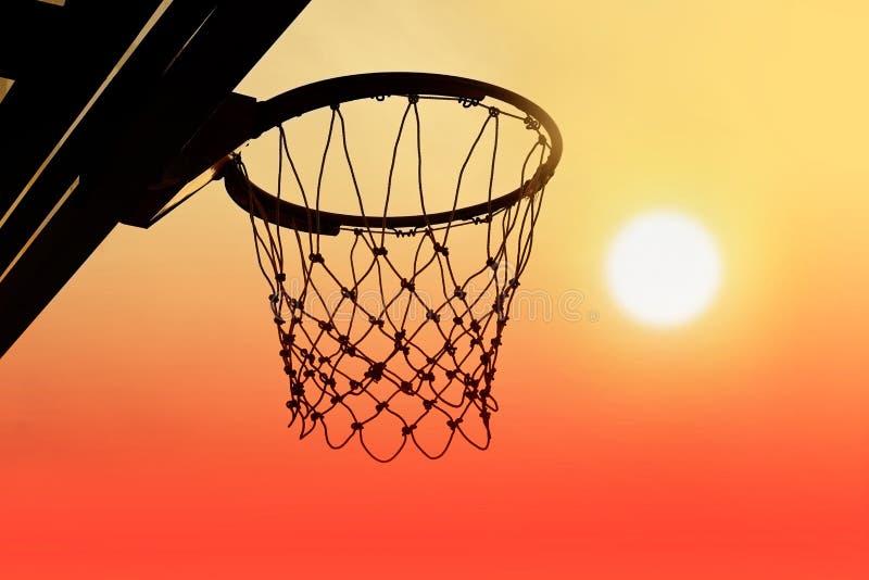 Cercle de basket-ball extérieur en silhouette de coucher du soleil photos libres de droits