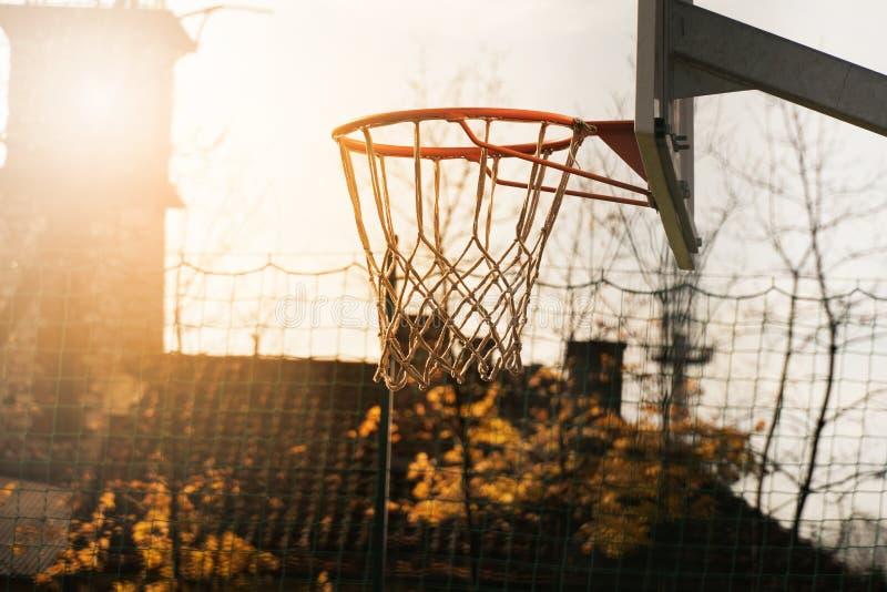 Cercle de basket-ball extérieur pour le sport collectif avec la lumière naturelle à l'arrière-plan d'automne d'arbre photos stock