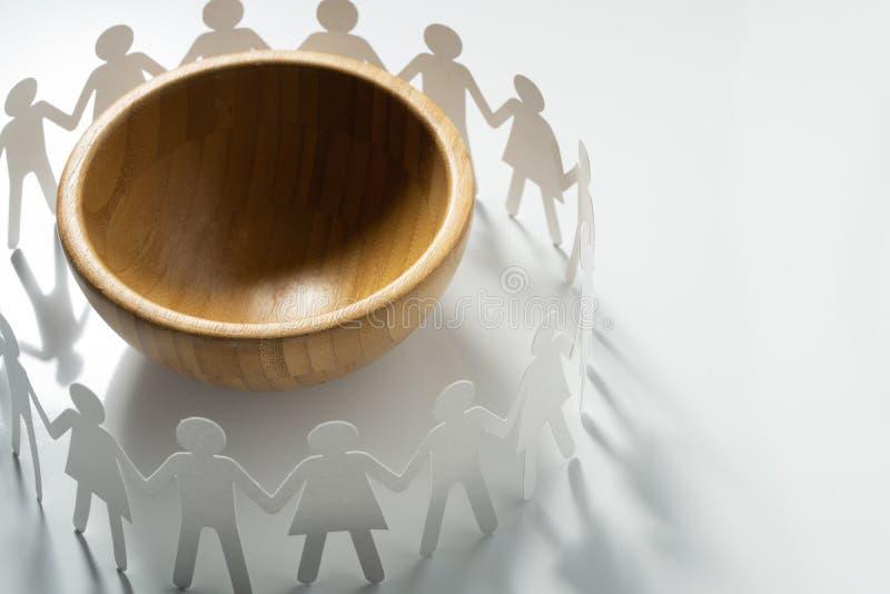 Cercle des personnes de papier tenant des mains devant la grande cuvette vide Surpopulation, concept de famine images libres de droits
