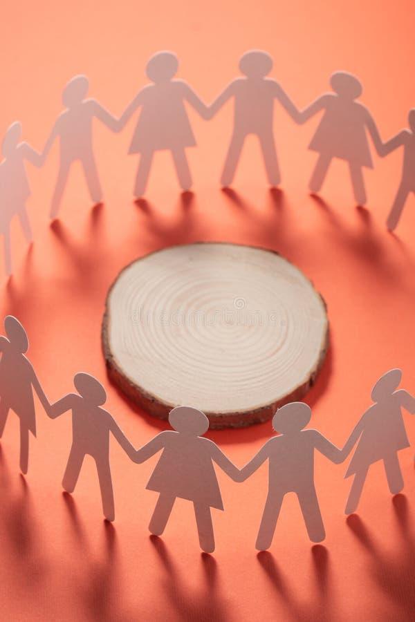 Cercle des personnes de papier tenant des mains devant la section transversale d'arbre Activisme, concept de conscience sociale photographie stock