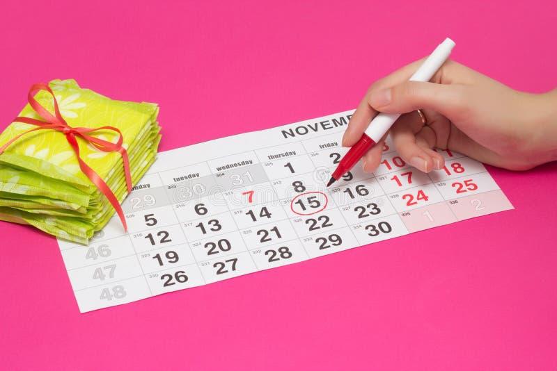 Cercle femelle de main les jours sur le calendrier avec un stylo feutre quand elle a sa période, fond rose, une pile de protectio photos libres de droits