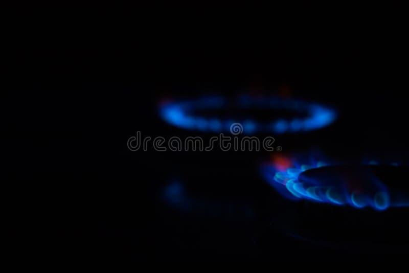 Cercles du feu sur une cuisinière à gaz dans l'obscurité Flamme bleue réfléchie sur la surface photo libre de droits