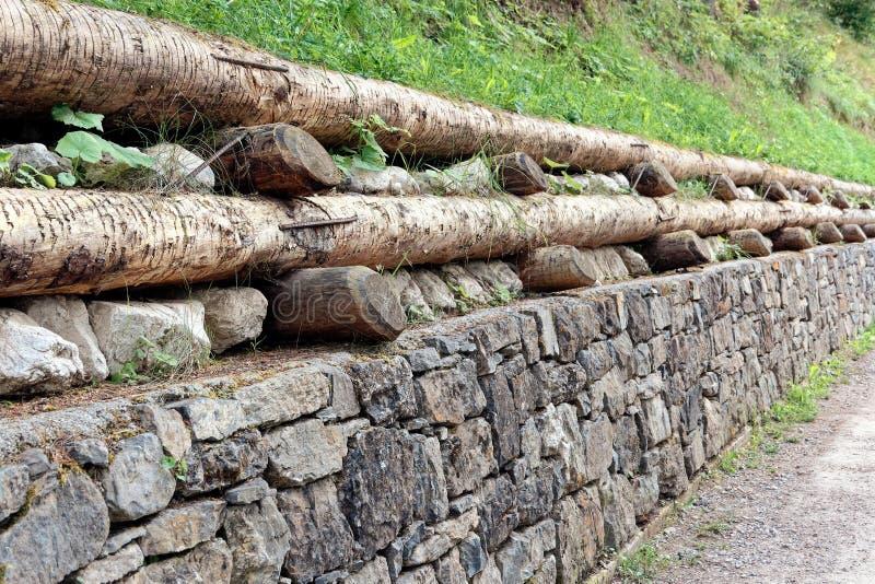 Cerco de pedra combinando a pedra e a madeira para a cerca foto de stock