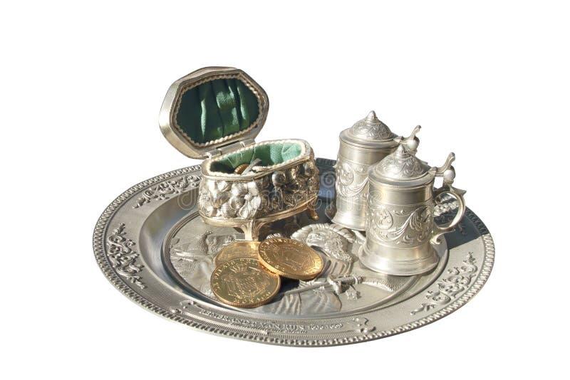 Cercueil avec des pièces de monnaie et de petits cercles sur le plateau marqueté en métal images stock