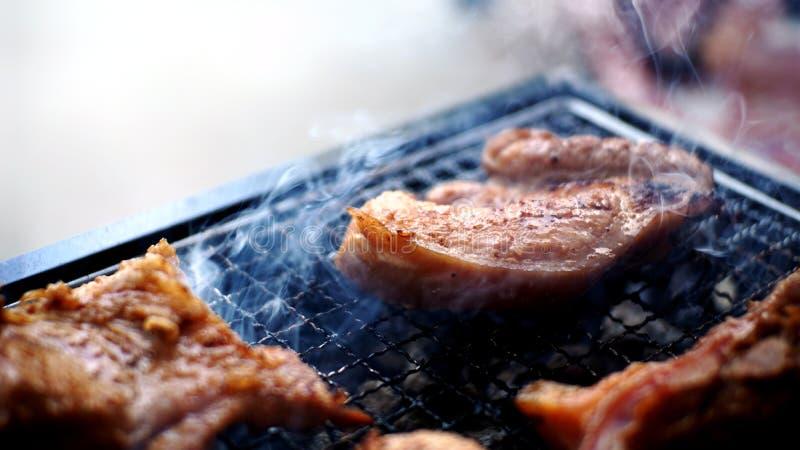 Cerdo asado a la parrilla con humo en el asador imagen de archivo