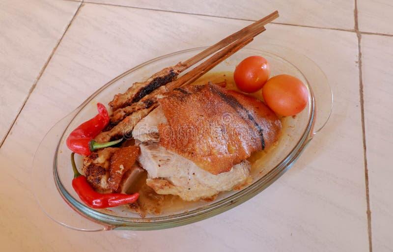 Cerdo de carne asada en una cacerola de cristal de la asación Carne picadita en un palillo de madera Piel crujiente y de oro-coci imágenes de archivo libres de regalías
