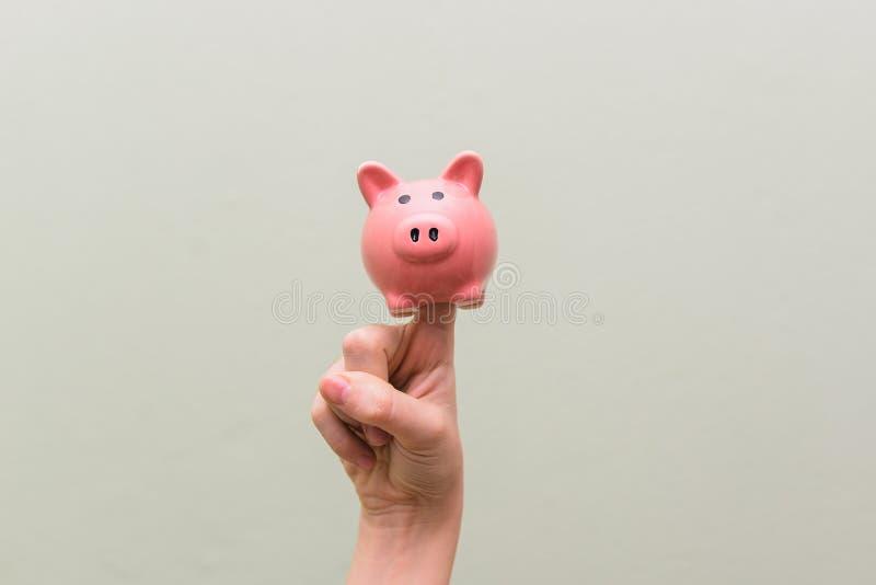 Cerdo de la porcelana en el dedo índice El concepto de dinero del ahorro Tema financiero imágenes de archivo libres de regalías