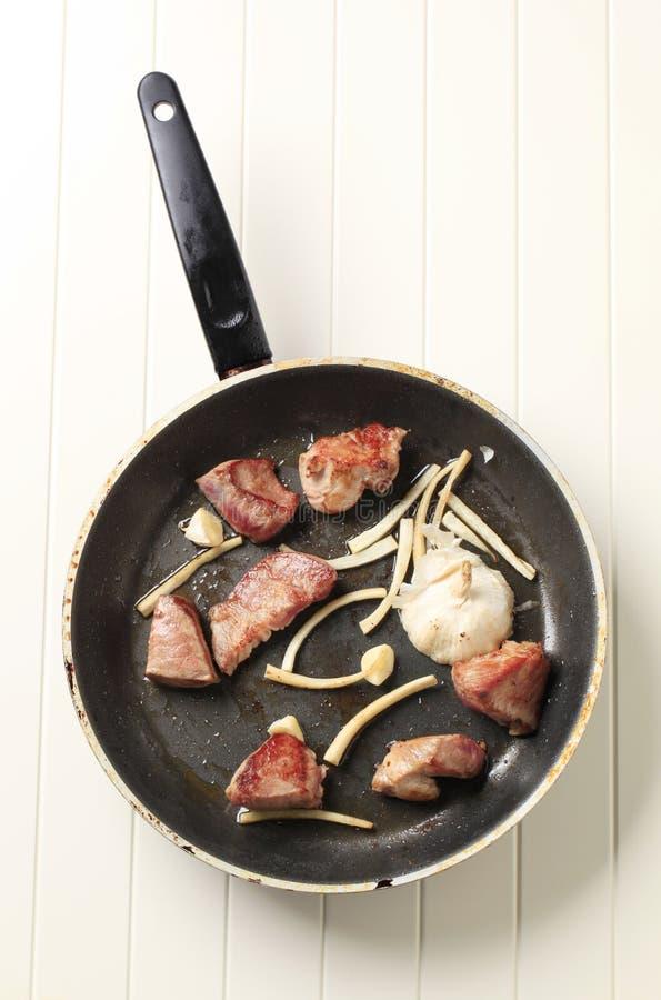 Cerdo y ajo del freído en cazuela fotos de archivo
