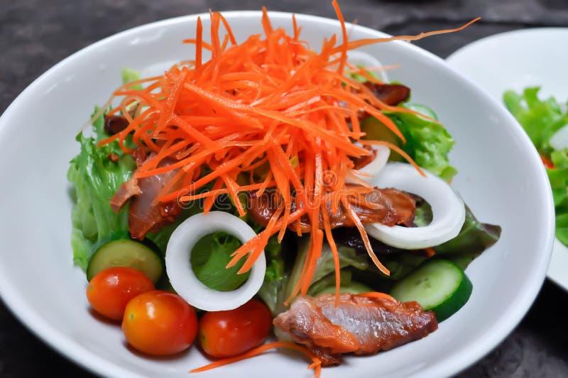 Cerdo y ensalada vegetal foto de archivo