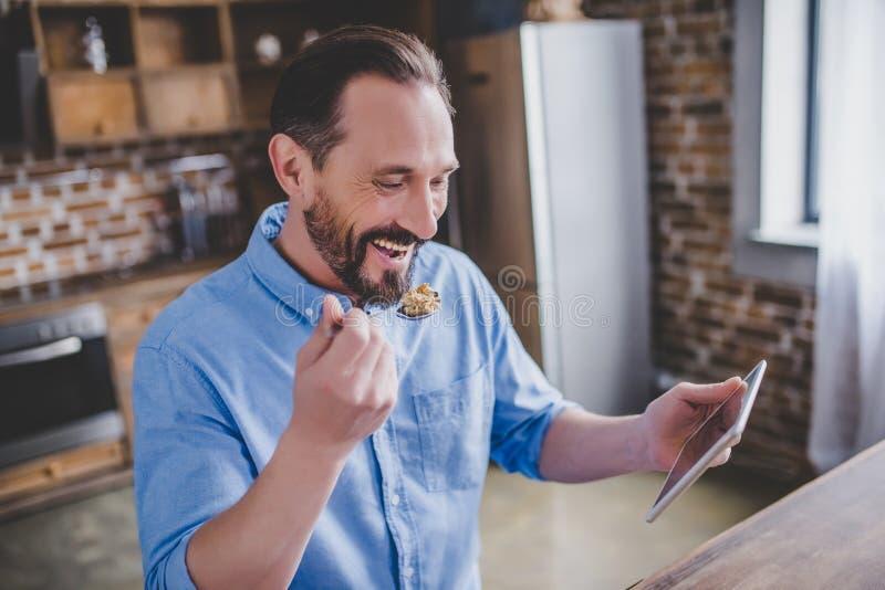 Cereais antropófagos e utilização da tabuleta digital fotografia de stock