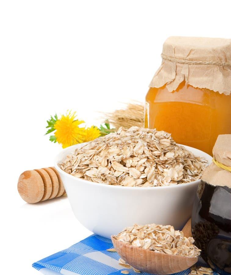 Cereais com o mel e o oatmeal isolados no branco fotografia de stock royalty free