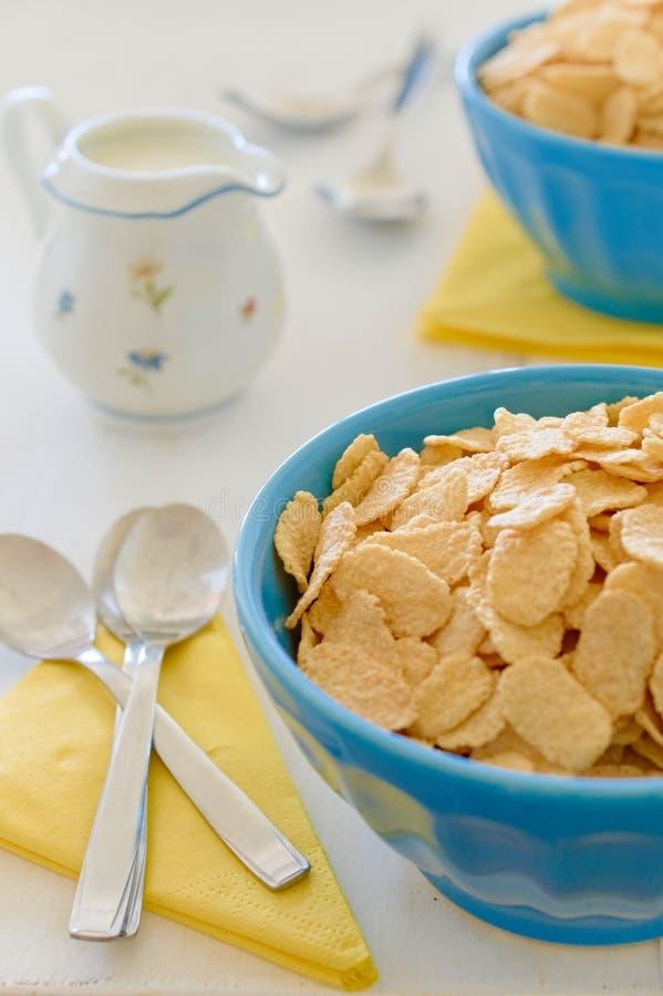 Cereais do milho com leite no potenciômetro cerâmico azul imagens de stock royalty free