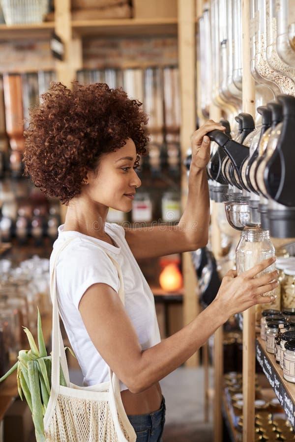 Cereais e grões da compra da mulher na mercearia livre plástica sustentável imagens de stock