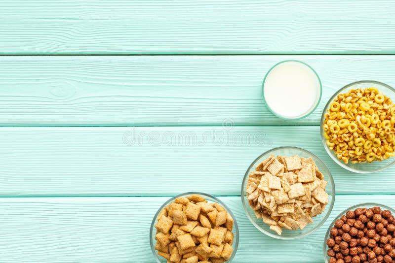 Cereais, oatflakes e flocos de milho com leite para o café da manhã saudável na zombaria de madeira da opinião superior do fundo  fotos de stock