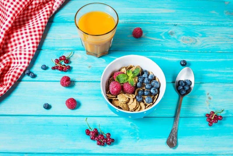 Cereais saudáveis do wholewheat de Multigrain com baga fresca e um vidro do suco para o café da manhã foto de stock royalty free