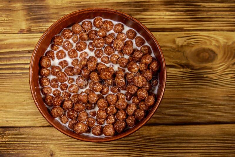 Cereal Chokladbollar med mjölk i en skål på träbord Överkant royaltyfria foton