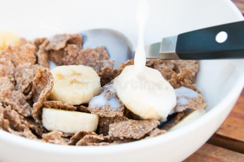 Cereal com o close up da banana e do leite foto de stock royalty free