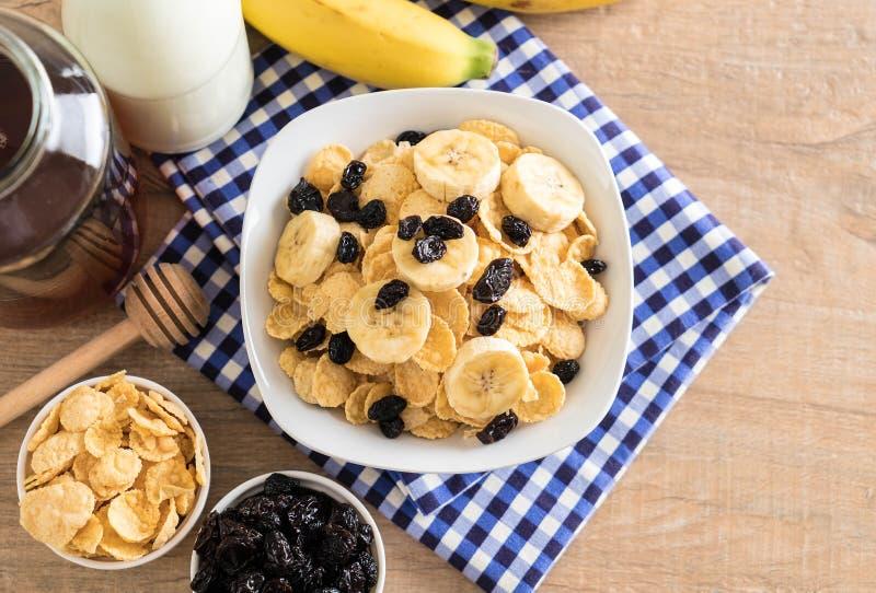 cereal con el plátano, la pasa y la leche imagen de archivo