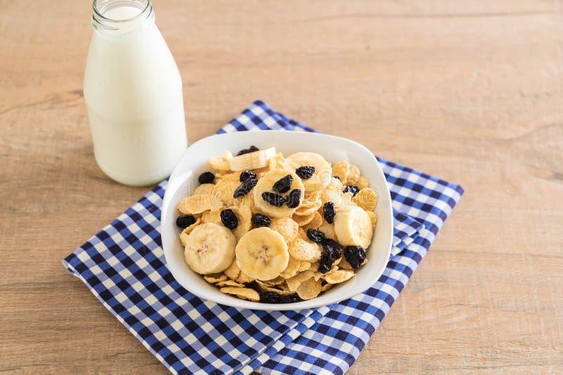 cereal con el pl?tano, la pasa y la leche foto de archivo