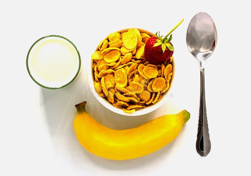 Cereal con leche y plátano y fresa en el fondo blanco fotografía de archivo libre de regalías