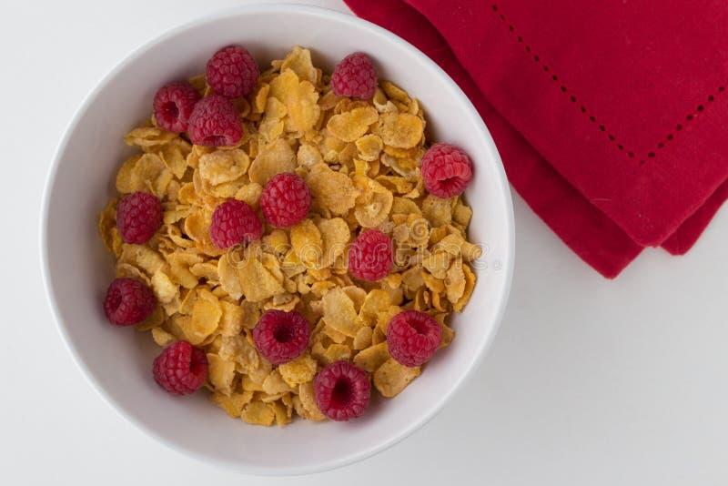 Cereal de desayuno de copos de maíz y de frambuesas en el backgrou blanco foto de archivo