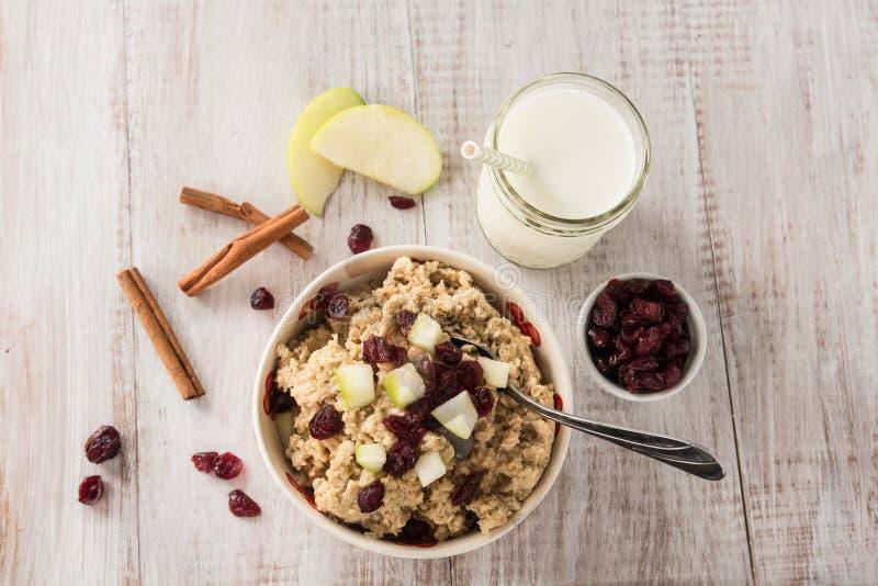 Cereal de desayuno de la harina de avena con los arándanos del canela y de las manzanas foto de archivo libre de regalías