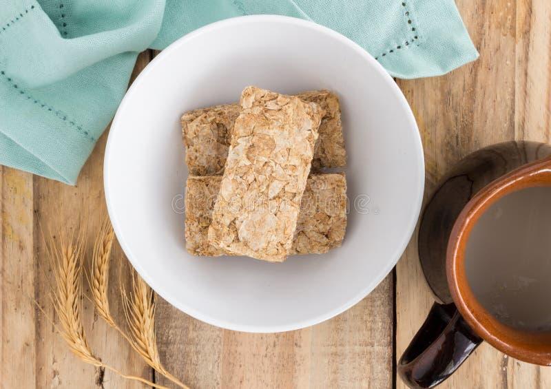 Cereal de desayuno del trigo crudo en cuenco en tablero de madera rústico imagenes de archivo