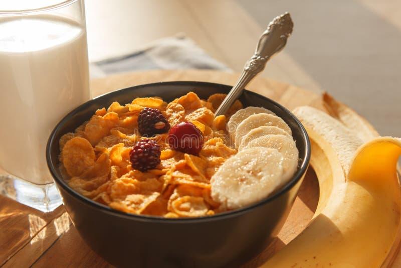 Cereal de desayuno de los copos de maíz en el cuenco con el vidrio de la leche, de bayas y del plátano en la tabla de madera foto de archivo libre de regalías