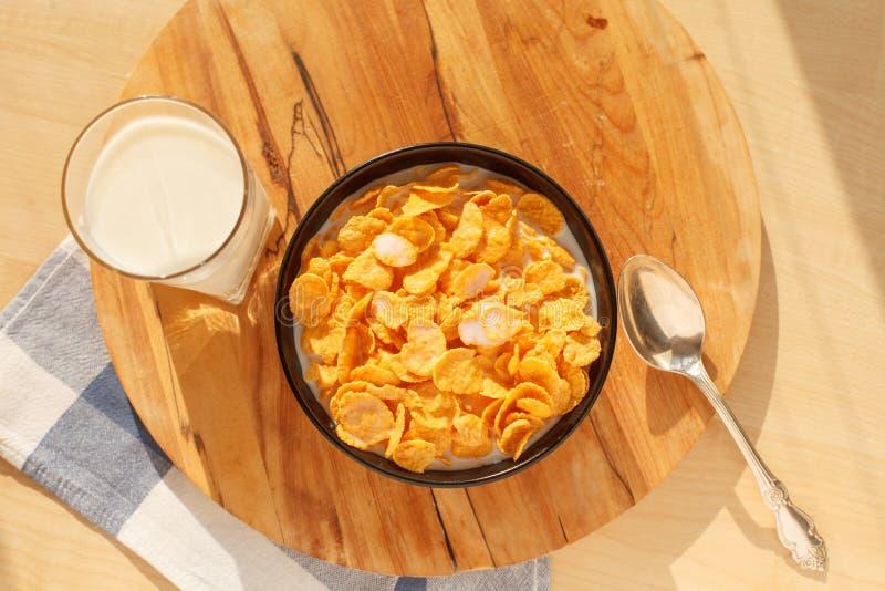 Cereal de desayuno de los copos de maíz en el cuenco con el vidrio de leche en la tabla de madera fotografía de archivo libre de regalías