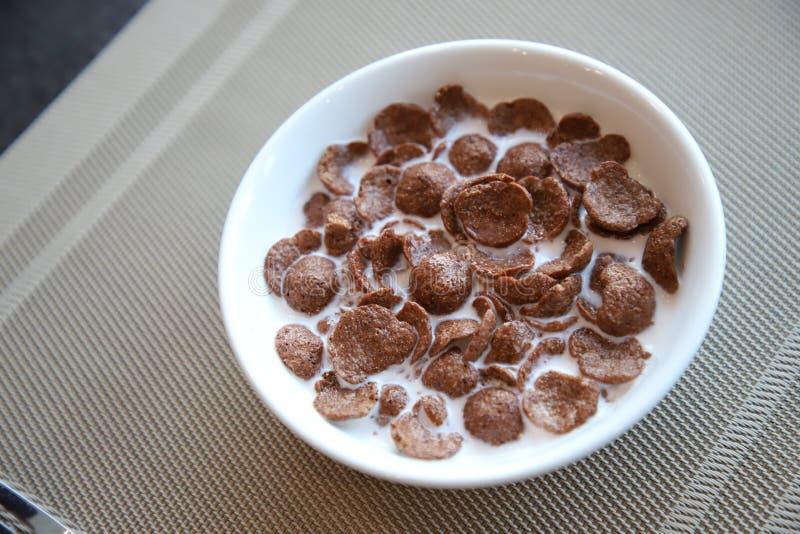 Cereal de los copos de maíz del chocolate del desayuno con leche en el cuenco blanco fotos de archivo
