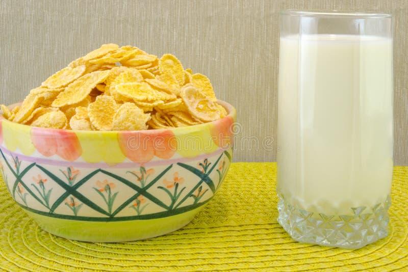Cereal de los copos de maíz en un cuenco y un vidrio de leche Desayuno de la mañana imágenes de archivo libres de regalías