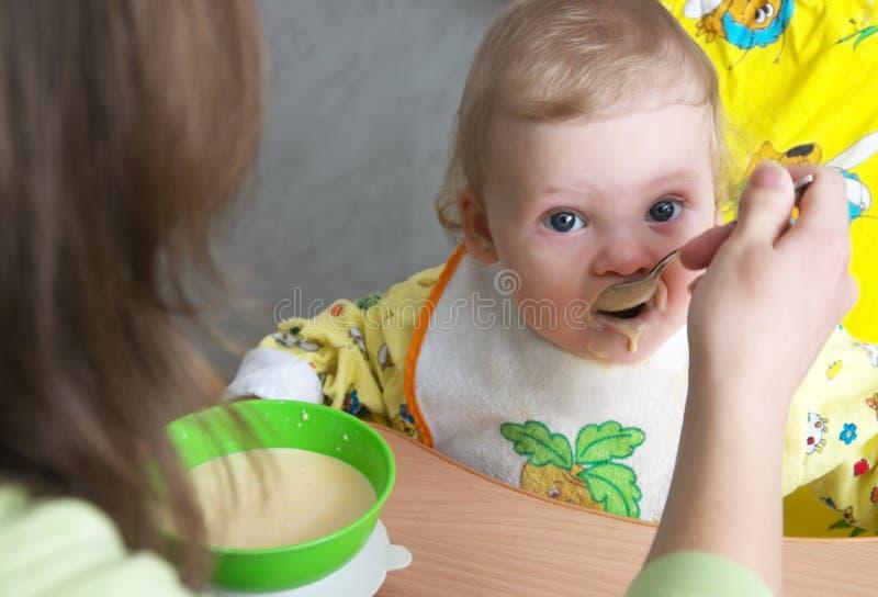 Cereal del bebé de la mama que introduce fotografía de archivo