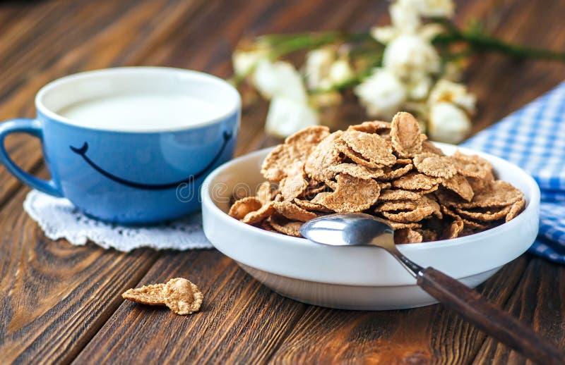 Cereal en el cuenco de cerámica blanco con la cuchara en la tabla de madera Escamas de Multigrain y taza de leche con sonrisa imagenes de archivo