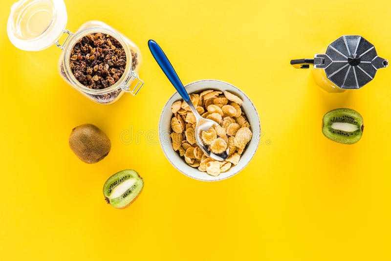 Cereal flakes in bowl and coffee maker with kiwis and raisins stock photos