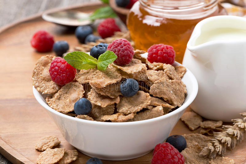 Cereal flakes with fresh berries, honey and milk for breakfast. Close-up royalty free stock photo