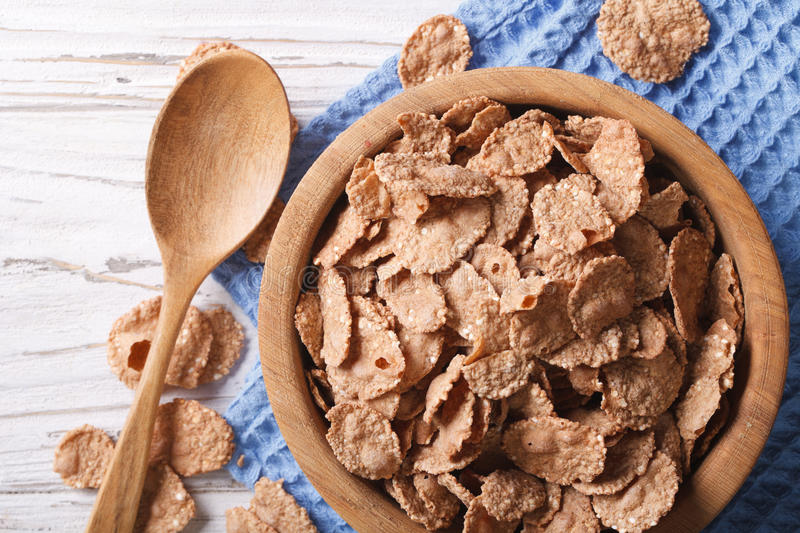 Cereal flakes in a wooden bowl closeup. Horizontal top view stock photos