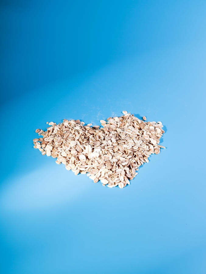 Cereal healthy breakfast. oat flakes in a heart shape,. Muesli on a blue background royalty free stock photo