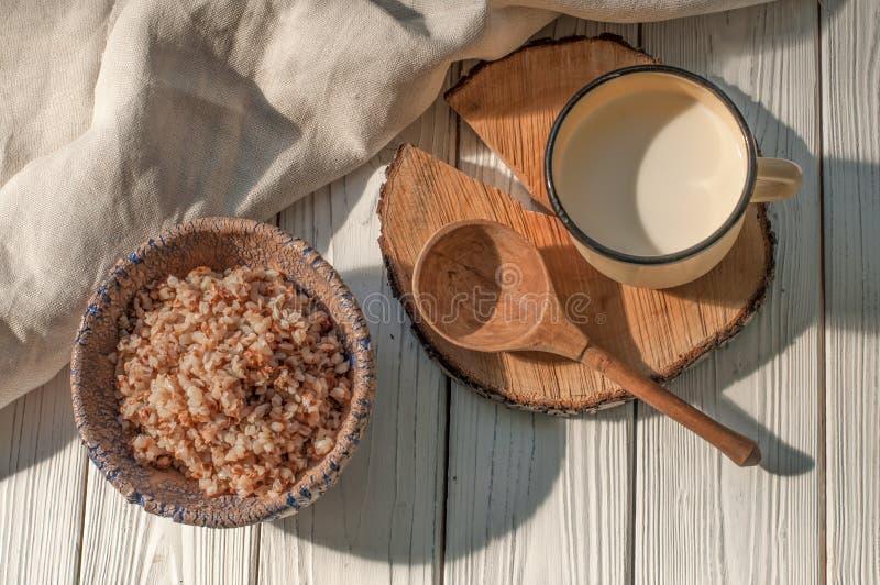Cereal hervido del alforfón en un cuenco de la cerámica, una taza del metal con leche y una cuchara de madera en una superficie d foto de archivo