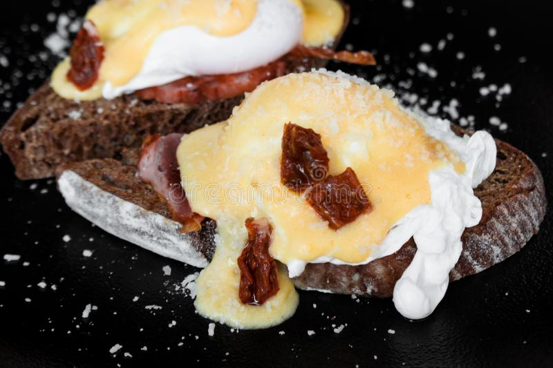 Cereal toast with fried bacon, egg Benedict and sun-dried tomato. Gourmet Breakfast with poached egg stock image