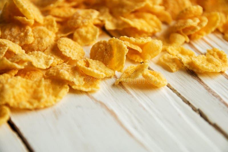 Cereal torrado dourado para o café da manhã em um fundo de madeira branco imagens de stock