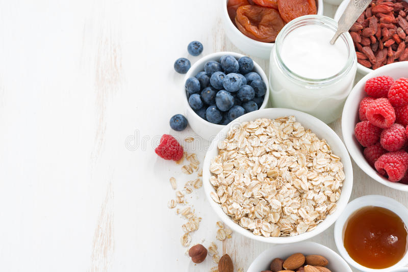 Cereal and various delicious ingredients for breakfast. And white wooden background, top view stock photo