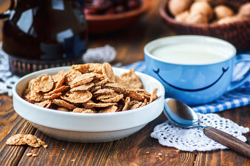 Cereal in white ceramic bowl with spoon on wooden table. Multigrain flakes and cup of milk with smile. Good morning or Have a nice day message concept. Healthy royalty free stock photos