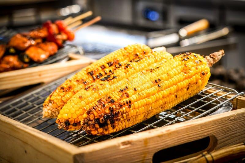 Cereale arrostito sulla griglia con il BBQ della sfuocatura accanto fotografie stock