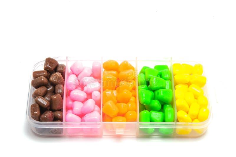 Cereale colorato sintetico per pescare Accessori per pesca della carpa sul fondo bianco fotografie stock