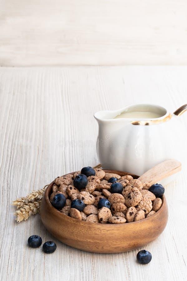 Cereale del biscotto di pepita di cioccolato con il mirtillo ed il latte sulla tavola di legno bianca immagini stock