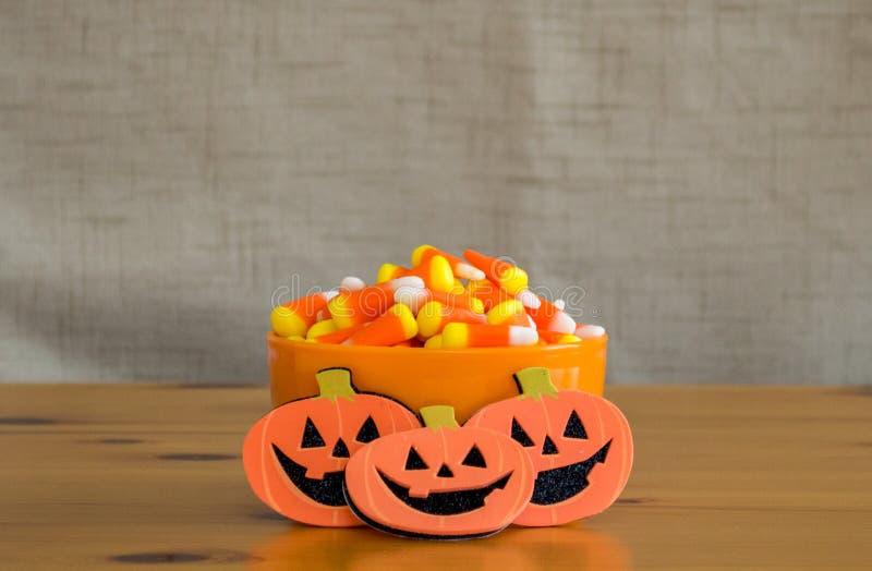 Cereale di Candy in una ciotola arancio con 3 presa-o-lanterne su una tavola di legno fotografia stock libera da diritti