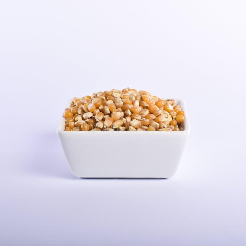 Cereale giallo per popcorn in una ciotola quadrata sui precedenti bianchi immagine stock