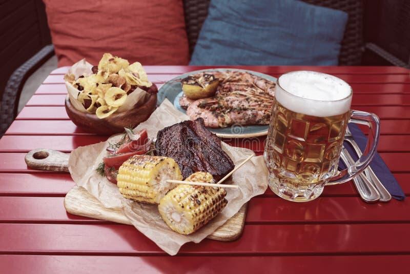 Cereale grigliato, costole calde del bbq con la tazza della birra chiara, tonificata fotografia stock