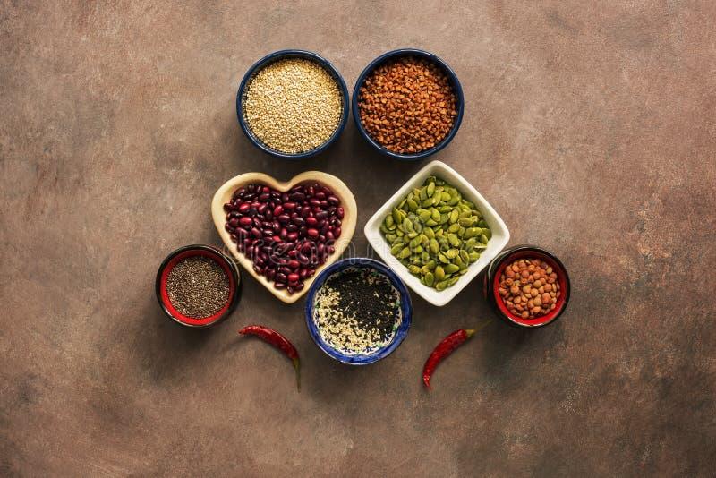 Cereales de la comida, legumbres, semillas y pimientas de chile estupendos en un fondo marrón Chia, quinoa, habas, alforfón, lent fotos de archivo