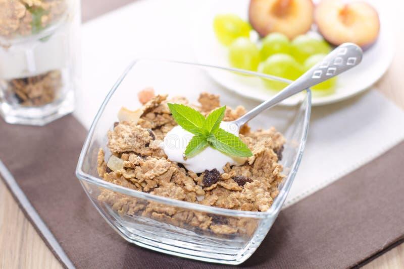 Cereales en un cuenco con el yogur, menta, fruta imagen de archivo